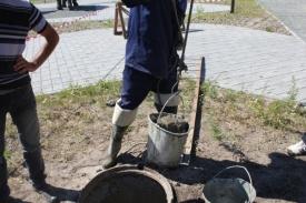 рабочие ведро земля канализационный люк Фото: управление общественный связей г. Ханты-Мансийск