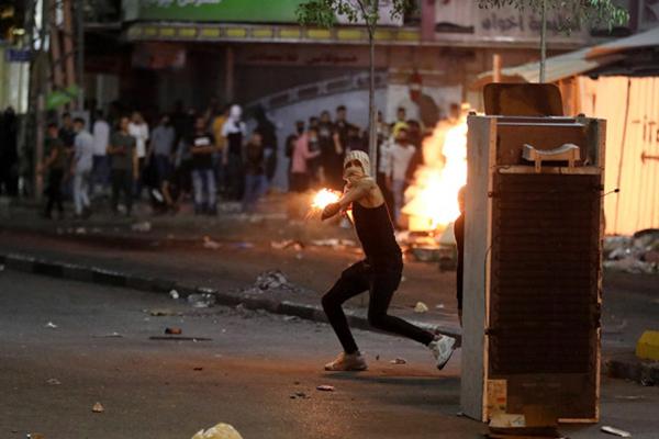 Палестинский демонстрант бросает коктейль Молотова в израильских солдат в городе Хеврон(2021)|Фото: Abed Al Hashlamoun / EPA / ТАСС